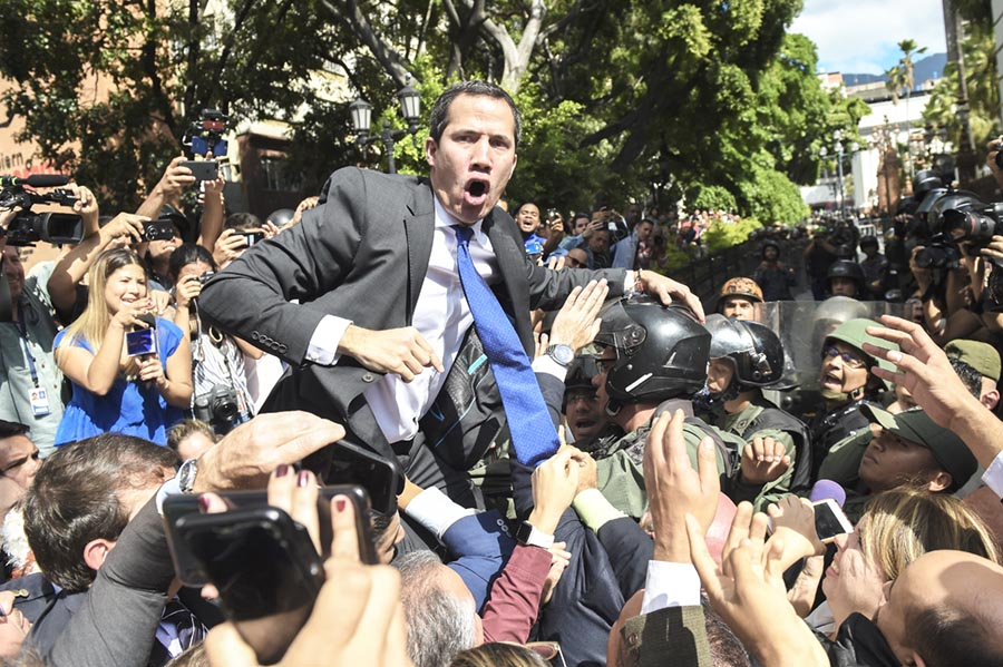 "Venezuelan opposition leader and self-proclaimed acting president Juan Guaido shouts surrounded by journalists on his way to the National Assembly, in Caracas, on January 7, 2020. - Opposition leader Juan Guaido and a rival lawmaker, Luis Parra -who both had claimed to be Venezuela's parliament speaker, following two separate votes and accusations of a ""parliamentary coup- called for a parliamentary session today. (Photo by Cristian Hernandez / AFP)"