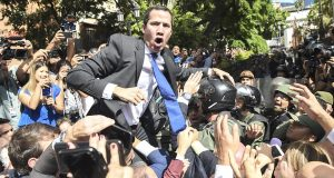 """Venezuelan opposition leader and self-proclaimed acting president Juan Guaido shouts surrounded by journalists on his way to the National Assembly, in Caracas, on January 7, 2020. - Opposition leader Juan Guaido and a rival lawmaker, Luis Parra -who both had claimed to be Venezuela's parliament speaker, following two separate votes and accusations of a """"parliamentary coup- called for a parliamentary session today. (Photo by Cristian Hernandez / AFP)"""